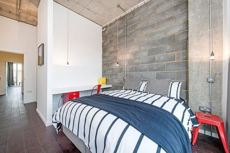 Industrial style London apartment - bedroom, bright furniture contrasts with the concrete wall