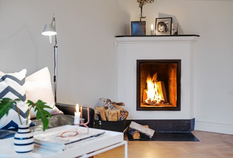 Decorate the zone around the fireplace - firewood candles and pictures in simple framework